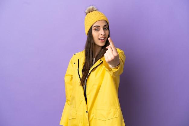 来たるジェスチャーをしている紫色の背景に分離された防雨コートを着ている若い白人女性