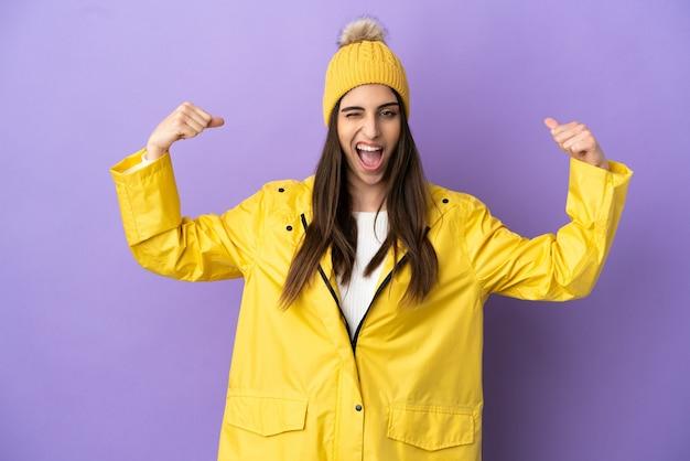 強いジェスチャーをしている紫色の背景に分離された防雨コートを着ている若い白人女性