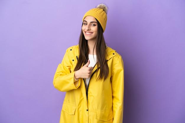 親指を立てるジェスチャーを与える紫色の背景に分離された防雨コートを着ている若い白人女性
