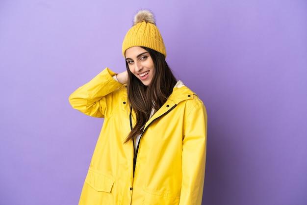 笑って紫色の背景に分離された防雨コートを着ている若い白人女性