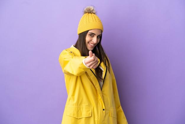 お金のジェスチャーを作る紫色の背景に分離された防雨コートを着ている若い白人女性
