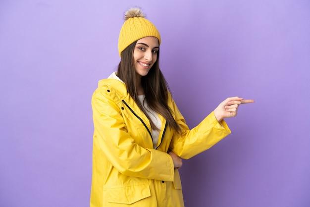 横に指を指している紫色の背景に分離された防雨コートを着ている若い白人女性