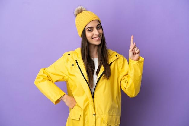 Молодая кавказская женщина в непромокаемом пальто на фиолетовом фоне показывает и поднимает палец в знак лучших