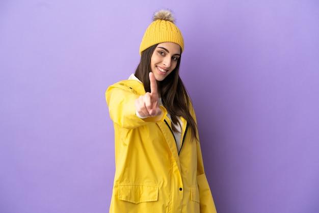 Молодая кавказская женщина в непромокаемом пальто на фиолетовом фоне показывает и поднимает палец