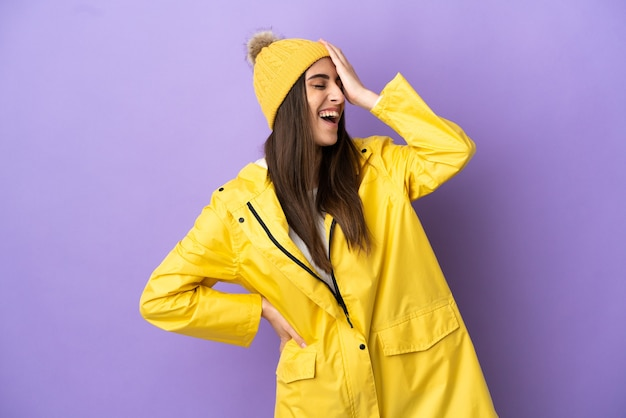 보라색 배경에 격리된 방수 코트를 입은 젊은 백인 여성이 많이 웃고 있습니다.