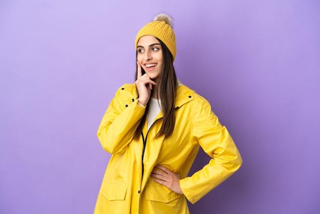 見上げながらアイデアを考えて紫色の背景に分離された防雨コートを着ている若い白人女性