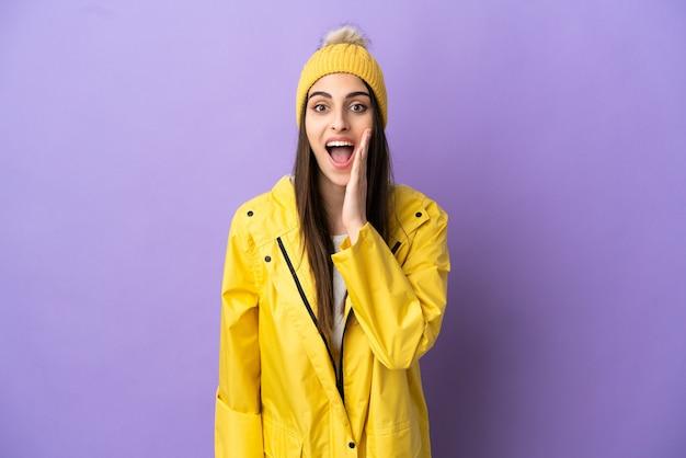 驚きとショックを受けた表情で紫色の背景に分離された防雨コートを着ている若い白人女性