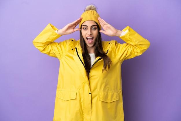 驚きの表情で紫色の背景に分離された防雨コートを着ている若い白人女性