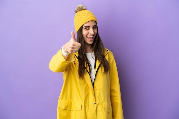 何か良いことが起こったので、親指を立てて紫色の背景で隔離の防雨コートを着ている若い白人女性