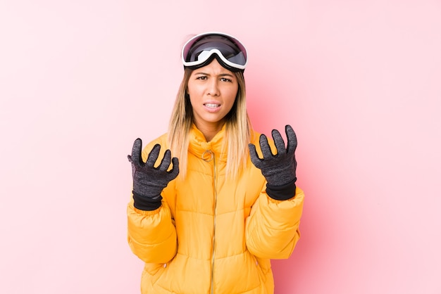 분홍색 벽에 스키 옷을 입고 젊은 백인 여자는 긴장된 손으로 비명 화가.