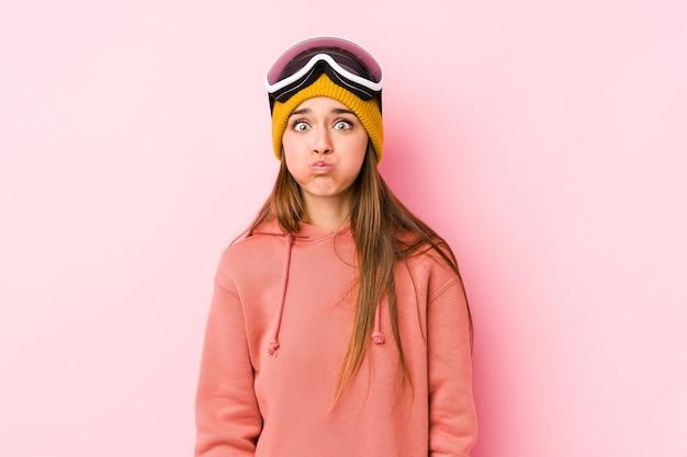 分離されたスキー服を着ている若い白人女性は頬を吹く、疲れた表情。顔の表情のコンセプトです。