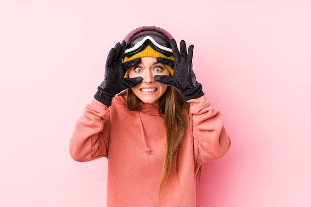 Молодая кавказская женщина в лыжной одежде изолировала глаза открытыми, чтобы найти возможность для успеха.