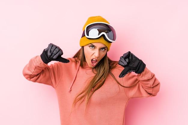 Молодая кавказская женщина в лыжной одежде изолировала, показывая большой палец вниз и выражая неприязнь.