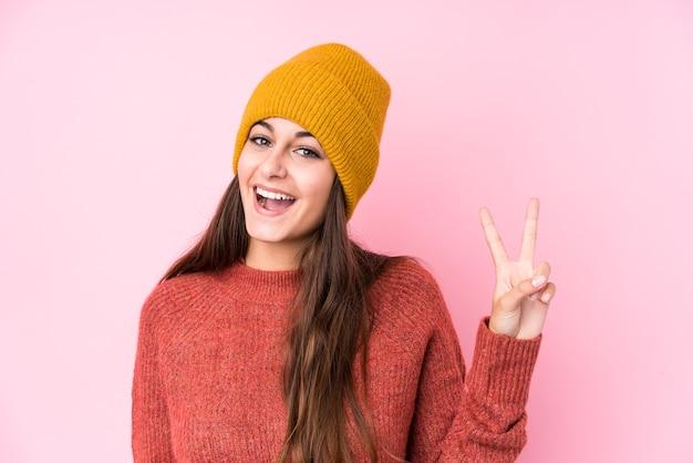 손가락으로 평화의 상징을 보여주는 즐겁고 평온한 모직 모자를 쓰고 젊은 백인 여자.