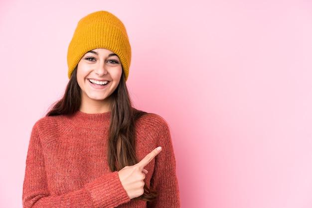 Молодая кавказская женщина в шерстяной кепке улыбается и показывает в сторону, показывая что-то на пустом месте.