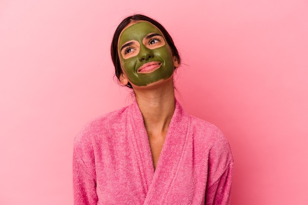 Young caucasian woman wearing a bathrobe and facial mask isolated on pink background dreaming of achieving goals and purposes