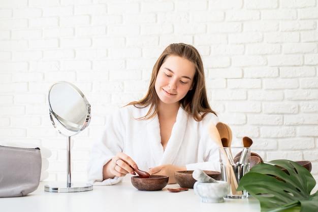 自然化粧品を使用してスパの手順を行うバスローブを着ている若い白人女性