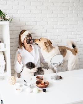 Молодая кавказская женщина в халатах делает спа-процедуры со своей собакой