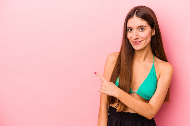 Young caucasian woman wearing bikini isolated on pink background smiling and pointing aside, showing something at blank space.
