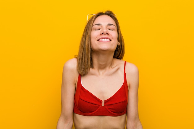 Young caucasian woman wearing bikini and sunglasses laughs and closes eyes, feels relaxed and happy.
