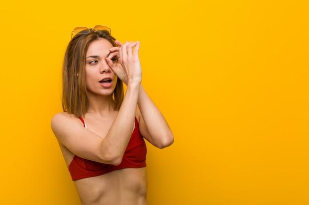 Young caucasian woman wearing bikini and sunglasses looking far away keeping her hand on forehead.