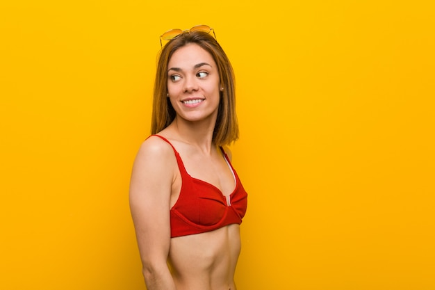 Young caucasian woman wearing bikini and sunglasses looks aside smiling, cheerful and pleasant.