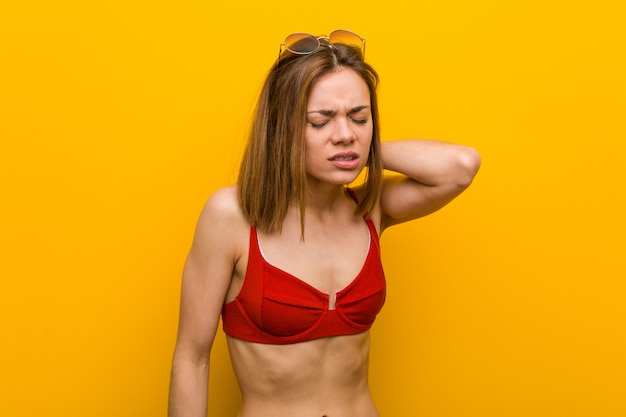 Young caucasian woman wearing bikini and sunglasses suffering neck pain