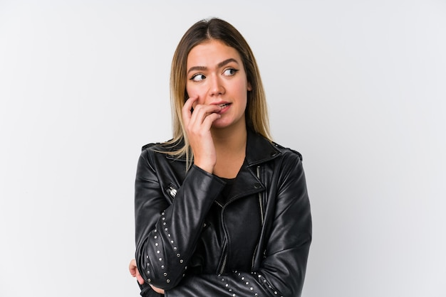 Young caucasian woman wearing a black leather jacket biting fingernails, nervous and very anxious.