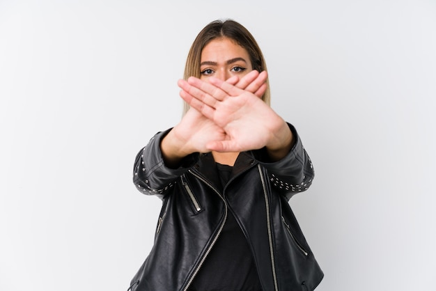 Young caucasian woman wearing a black leather jacket doing a denial gesture