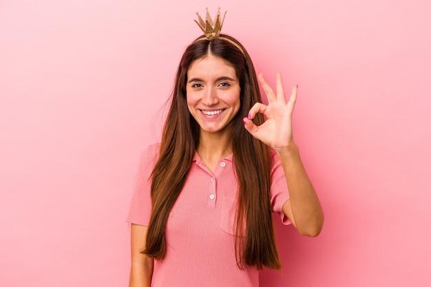 ピンクの背景に分離された王冠を身に着けている若い白人女性は、陽気で自信を持って大丈夫なジェスチャーを示しています。