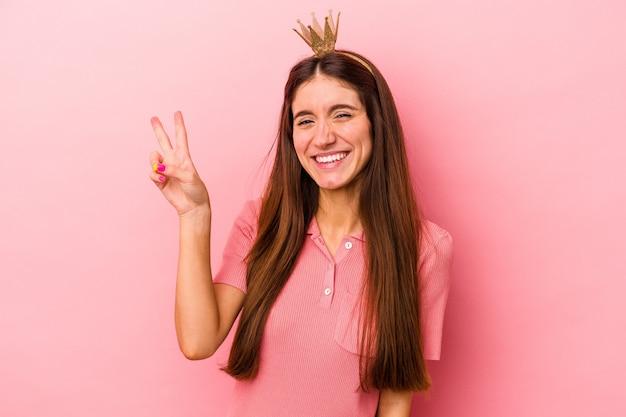 ピンクの背景に分離された王冠を身に着けている若い白人女性は、指で平和のシンボルを喜んで気楽に示しています。