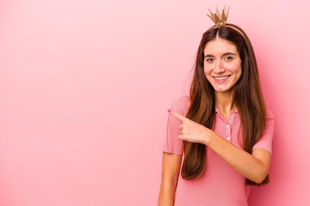 ピンクの背景に分離された王冠を身に着けている若い白人女性が笑顔で脇を指して、空白のスペースで何かを示しています。