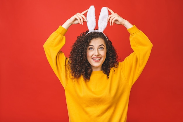 Young caucasian woman wearing cute easter rabbit ears over red isolated background while smiling confident and happy.