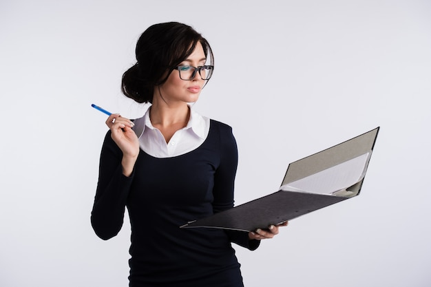 Young caucasian woman wearing dark blue dress, white shirt, holding a ring binder folder and pen.