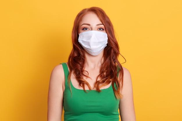 黄色のスペースで分離されたcovid 19から保護するためにフェイスマスクを着ている若い白人女性は、ドレスの緑のシャツ