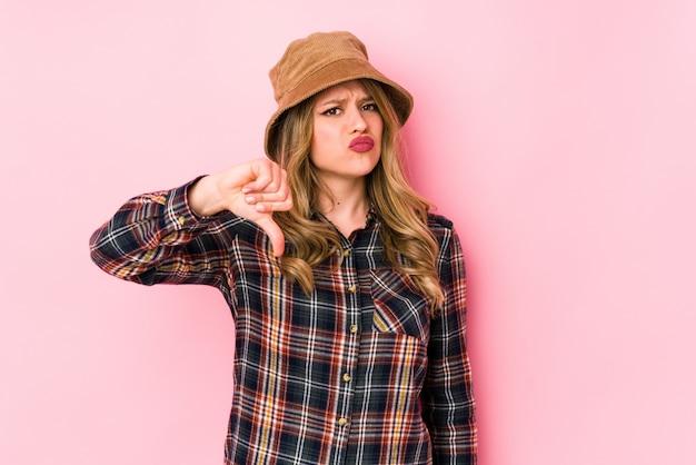 Young caucasian woman wearing a hat showing thumb down
