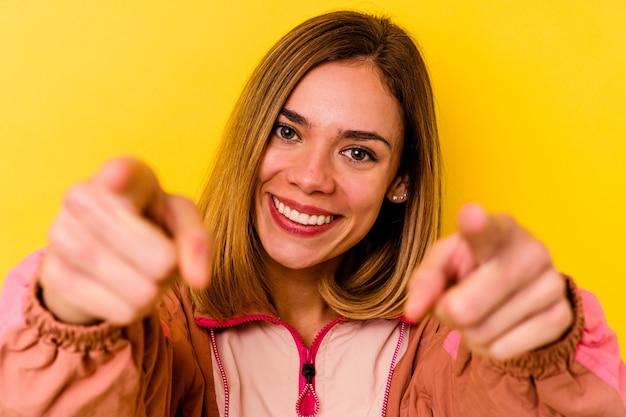 黄色の壁に分離された目に見えない矯正歯科を身に着けている若い白人女性