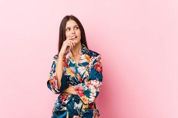 Young caucasian woman wearing a kimono pajama relaxed thinking about something looking at a copy space.