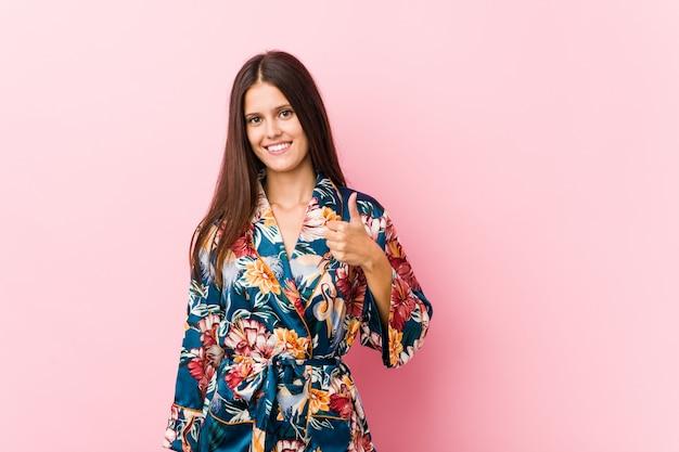 Young caucasian woman wearing a kimono pajama smiling and raising thumb up