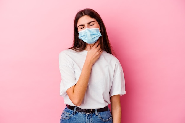 Young caucasian woman wearing a mask for virus isolated on pink wall suffers pain in throat due a virus or infection.