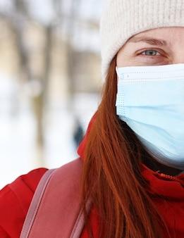 街の通りでカメラを見ている医療マスクを身に着けている若い白人女性。コロナウイルスの発生時の公共の場所での安全性。