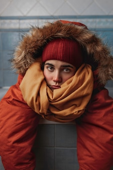 Young caucasian woman wearing an orange coat, a yellow scarf and a red winter hat is leaned and resting inside a bathtub in a bathroom with blue tiles and a neutral expression.