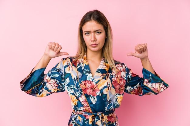 Молодая кавказская женщина в пижаме чувствует гордость и уверенность в себе, пример для подражания.