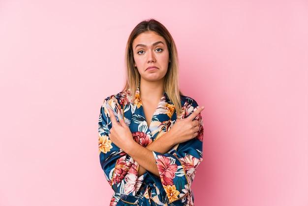 パジャマを着た若い白人女性が横向きのポイント、2つのオプションから選択しようとしています。