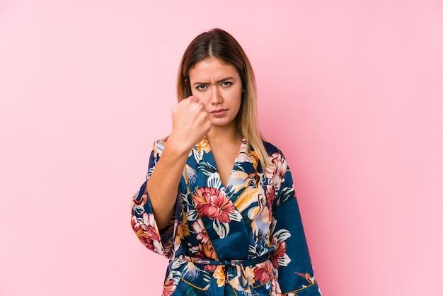 Молодая кавказская женщина в пижаме показывает кулак, агрессивное выражение лица.
