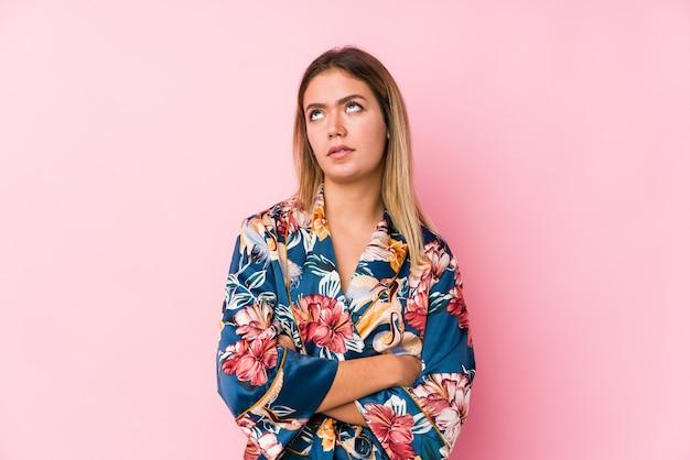 繰り返しの仕事にうんざりしているパジャマを着ている若い白人女性。