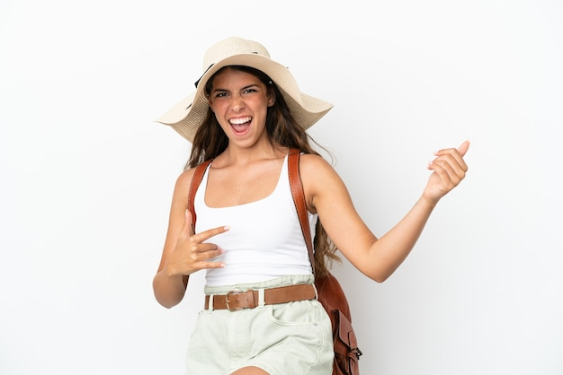 Young caucasian woman wearing a pamela in summer holidays isolated on white background making guitar gesture