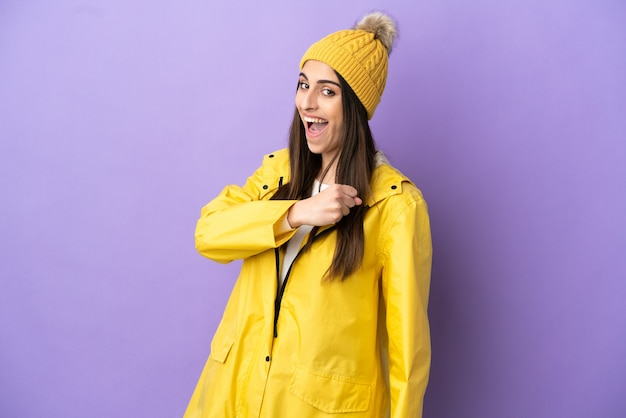 Young caucasian woman wearing a rainproof coat isolated on purple background celebrating a victory