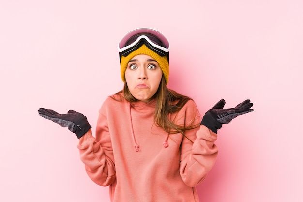 Young caucasian woman wearing a ski clothes isolated confused and doubtful shrugging shoulders to hold a copy space.