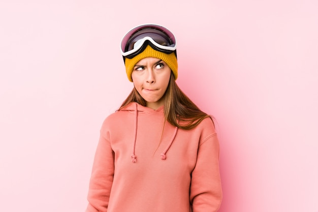 Young caucasian woman wearing a ski clothes isolated confused, feels doubtful and unsure.